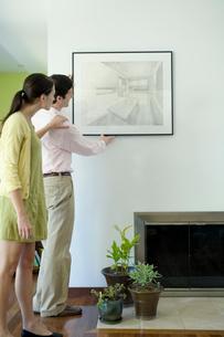 壁に絵を飾るカップルの写真素材 [FYI03954558]