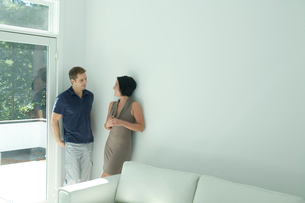 壁際で話をするカップルの写真素材 [FYI03954566]