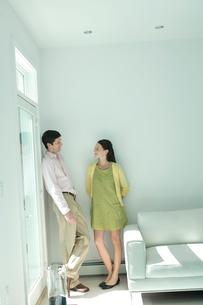 壁際で話をするカップルの写真素材 [FYI03954567]