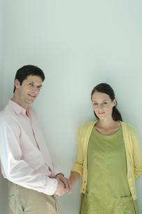 壁際で手を取り合うカップルの写真素材 [FYI03954568]