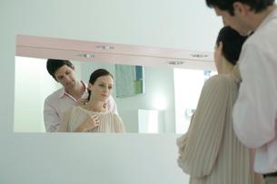 鏡を見ながら女性にネックレスをつける男性の写真素材 [FYI03954579]