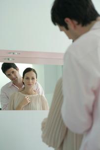 鏡を見ながら女性にネックレスをつける男性の写真素材 [FYI03954581]