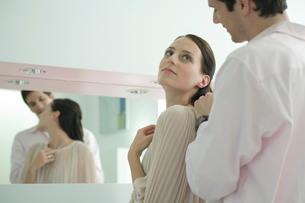 鏡を見ながら女性にネックレスをつける男性の写真素材 [FYI03954582]