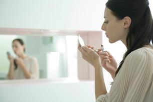 口紅を塗る女性の写真素材 [FYI03954589]