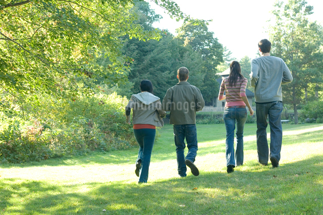 公園を歩くカップル2組の後ろ姿の写真素材 [FYI03954612]