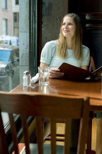 テーブルに座り外を見る女性の写真素材 [FYI03954618]
