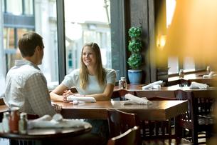 テーブルで談笑するカップルの写真素材 [FYI03954640]