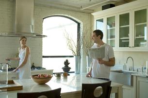 キッチンで談笑するカップルの写真素材 [FYI03954657]