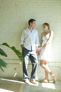 壁際で談笑するカップルの写真素材 [FYI03954668]