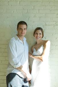 壁際で微笑むカップルの写真素材 [FYI03954670]