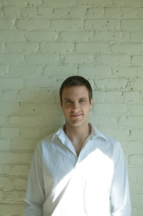 壁際で微笑む男性の写真素材 [FYI03954672]