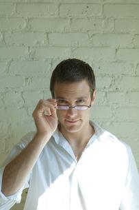 壁際で眼鏡をかける男性の写真素材 [FYI03954673]