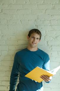 壁際で本を読む男性の写真素材 [FYI03954675]