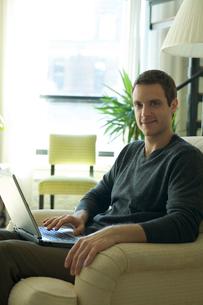 ソファでコンピュータをする男性の写真素材 [FYI03954687]