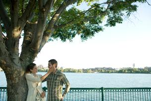 木のそばで談笑するカップルの写真素材 [FYI03954701]