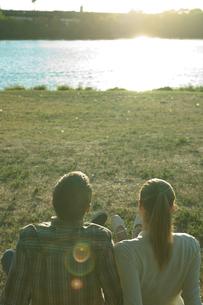 川原に座るカップルの後ろ姿の写真素材 [FYI03954708]