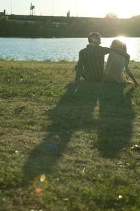川原に座るカップルの後ろ姿の写真素材 [FYI03954710]