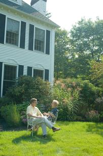 庭で椅子に座り談笑するシニアカップルの写真素材 [FYI03954726]