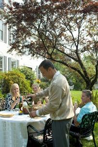 庭で食事をするシニアカップル2組の写真素材 [FYI03954779]