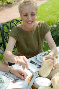 パンを取るシニア女性の写真素材 [FYI03954782]