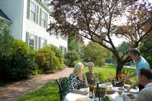 庭で食事をするシニアカップル2組の写真素材 [FYI03954784]
