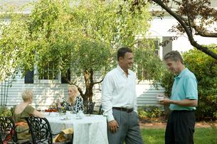 庭で談笑するシニアカップル2組の写真素材 [FYI03954795]
