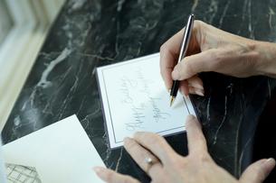 カードを書くシニア女性の手元の写真素材 [FYI03954805]