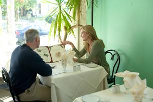 レストランでメニューを見るシニアカップルの写真素材 [FYI03954869]