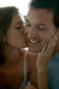 男性の頬にキスをする女性の写真素材 [FYI03954908]