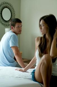 ベッドの上で女性を見つめる男性の写真素材 [FYI03954921]