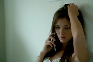 壁際で携帯電話で話す女性の写真素材 [FYI03954950]