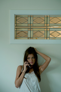 壁際で携帯電話で話す女性の写真素材 [FYI03954951]