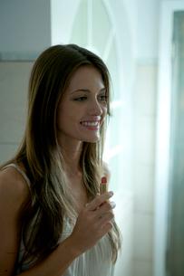 バスルームで口紅をつける女性の写真素材 [FYI03954970]