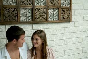 壁際で楽しく会話をするカップルの写真素材 [FYI03954980]
