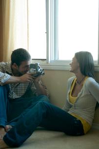 窓際で女性を撮影する男性の写真素材 [FYI03955001]
