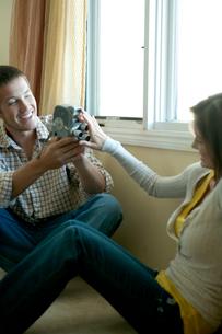 窓際で女性を撮影する男性の写真素材 [FYI03955002]