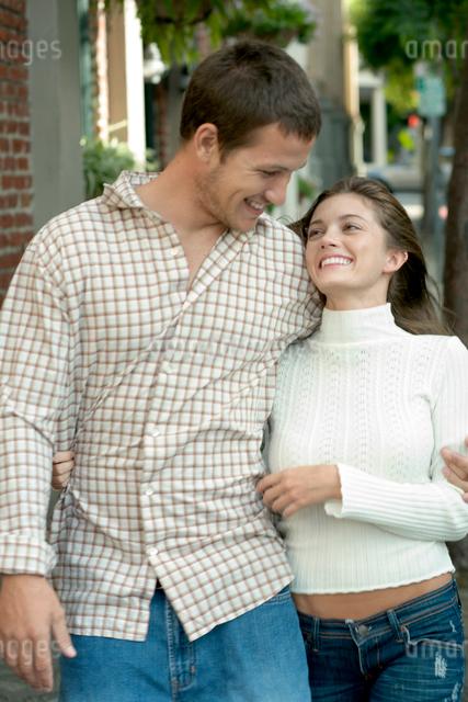 レンガ壁の前を楽しそうに歩くカップルの写真素材 [FYI03955004]