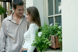 白い建物の窓際で会話をするカップルの写真素材 [FYI03955006]
