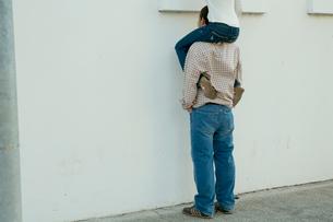 白い壁際で女性を肩車する男性の写真素材 [FYI03955007]