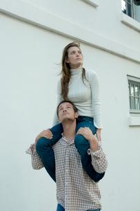 白い壁際で女性を肩車する男性の写真素材 [FYI03955008]