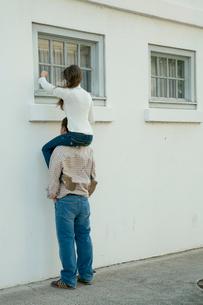 男性の肩に乗って窓をノックする女性の写真素材 [FYI03955010]