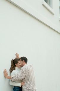 白い壁際でささやくカップルの写真素材 [FYI03955013]