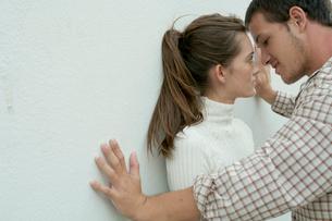 白い壁際でキスをしようとするカップルの写真素材 [FYI03955014]