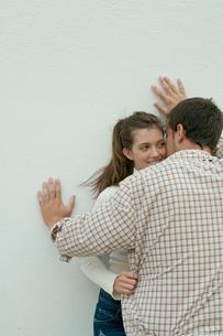 白い壁際でささやくカップルの写真素材 [FYI03955015]
