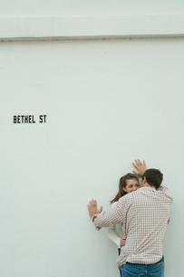 白い壁際でささやくカップルの写真素材 [FYI03955016]