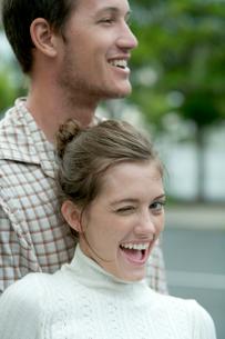男性に寄りかかってウィンクをする女性の写真素材 [FYI03955017]