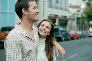 街中を笑顔で散歩するカップルの写真素材 [FYI03955020]