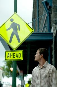 道路標識を見つめる男性の写真素材 [FYI03955023]