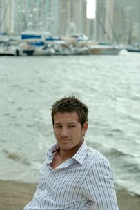 海沿いに座ってリラックスする男性の写真素材 [FYI03955029]