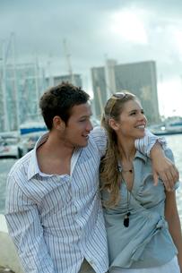 海沿いを肩を組んで歩くカップルの写真素材 [FYI03955030]
